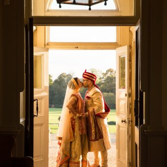 36 wedding photography London Hindu wedding doorway kiss