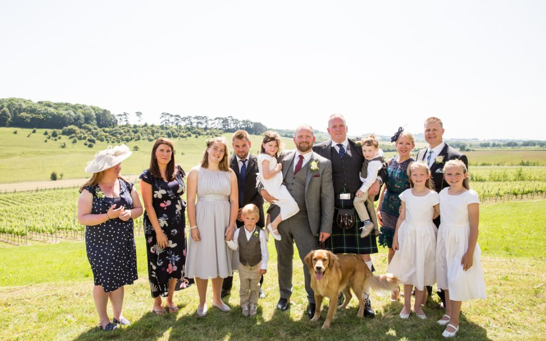 Two grooms with best man, best woman, flower girls and wedding dog